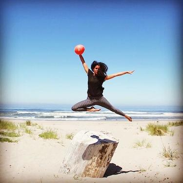 Liz Richards, Acupuncturist and Blossom owner, taking a leap with her barre3 core ball.